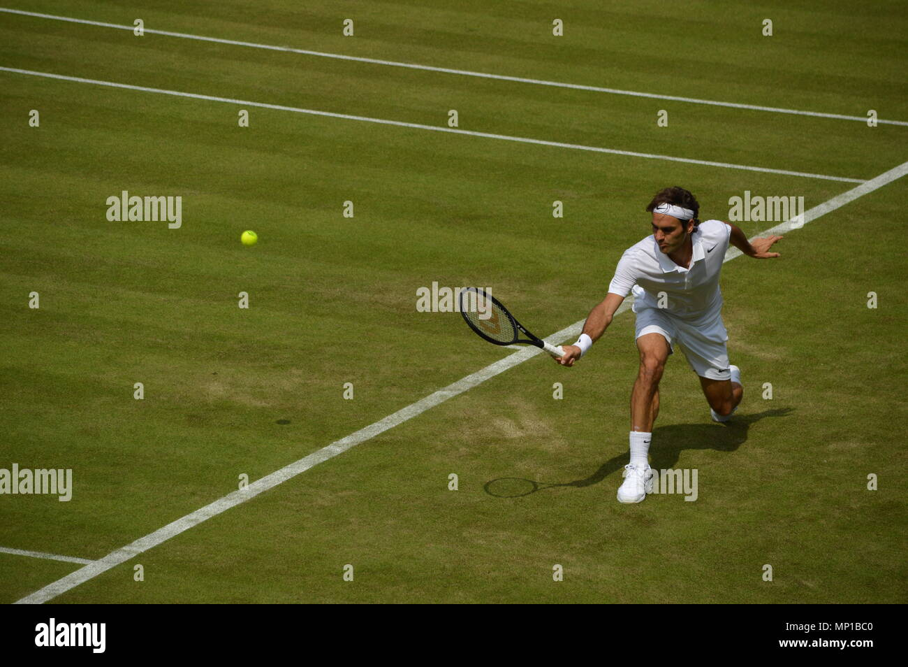 Roger Federer returning a shot with a backhand at Wimbledon - Stock Image