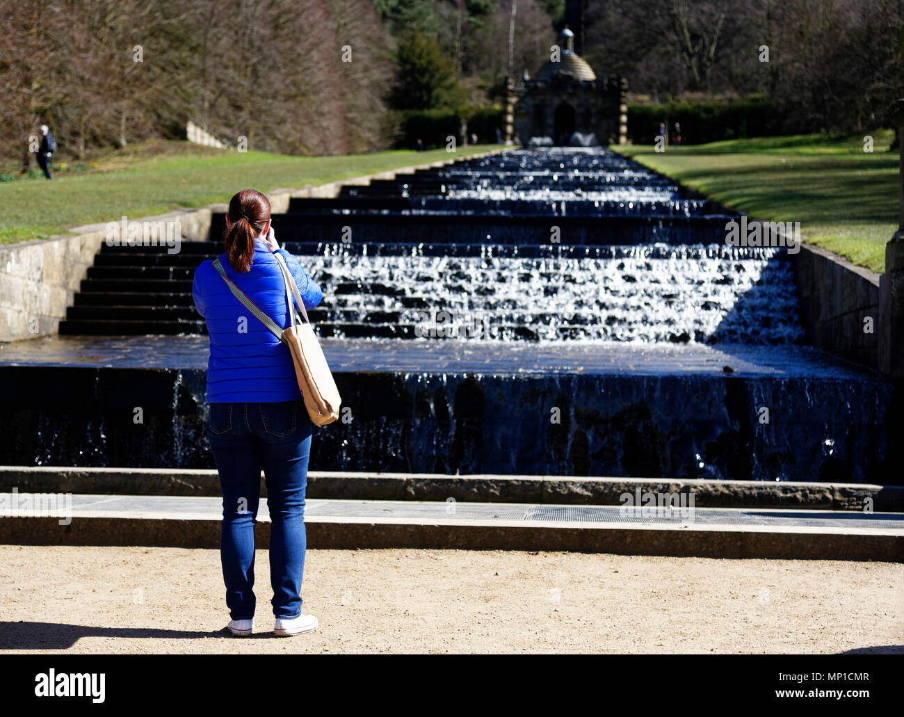 A lady tourist taking a photo of The Cascade in the grounds of Chatsworth House near Bakewell in Derbyshire - Stock Image