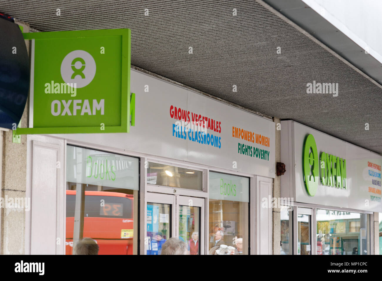 Oxfam shop front, with the slogans 'Empowers Women', 'Fights Poverty', 'Grows Vegetables' and 'Fills Classrooms' - Stock Image