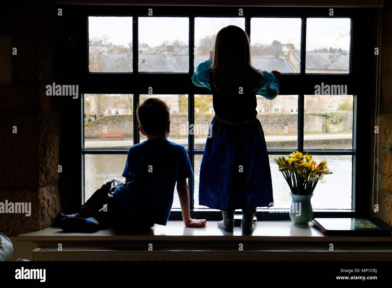 Brother (5 yrs old) and sister (3 yrs old) sat on a window sill, silhouetted against a sash window with the River Wye in Bakewell outside - Stock Image