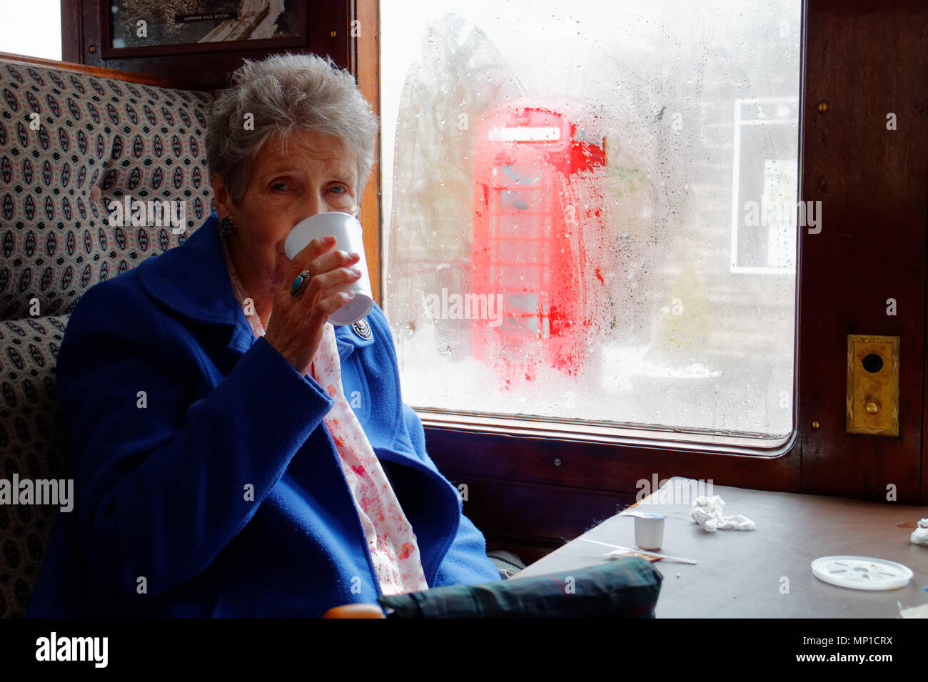 An older woman drinking tea on the Peak Rail steam train on a rainy day in in Bakewell, Derbyshire with a red phone box outside - Stock Image