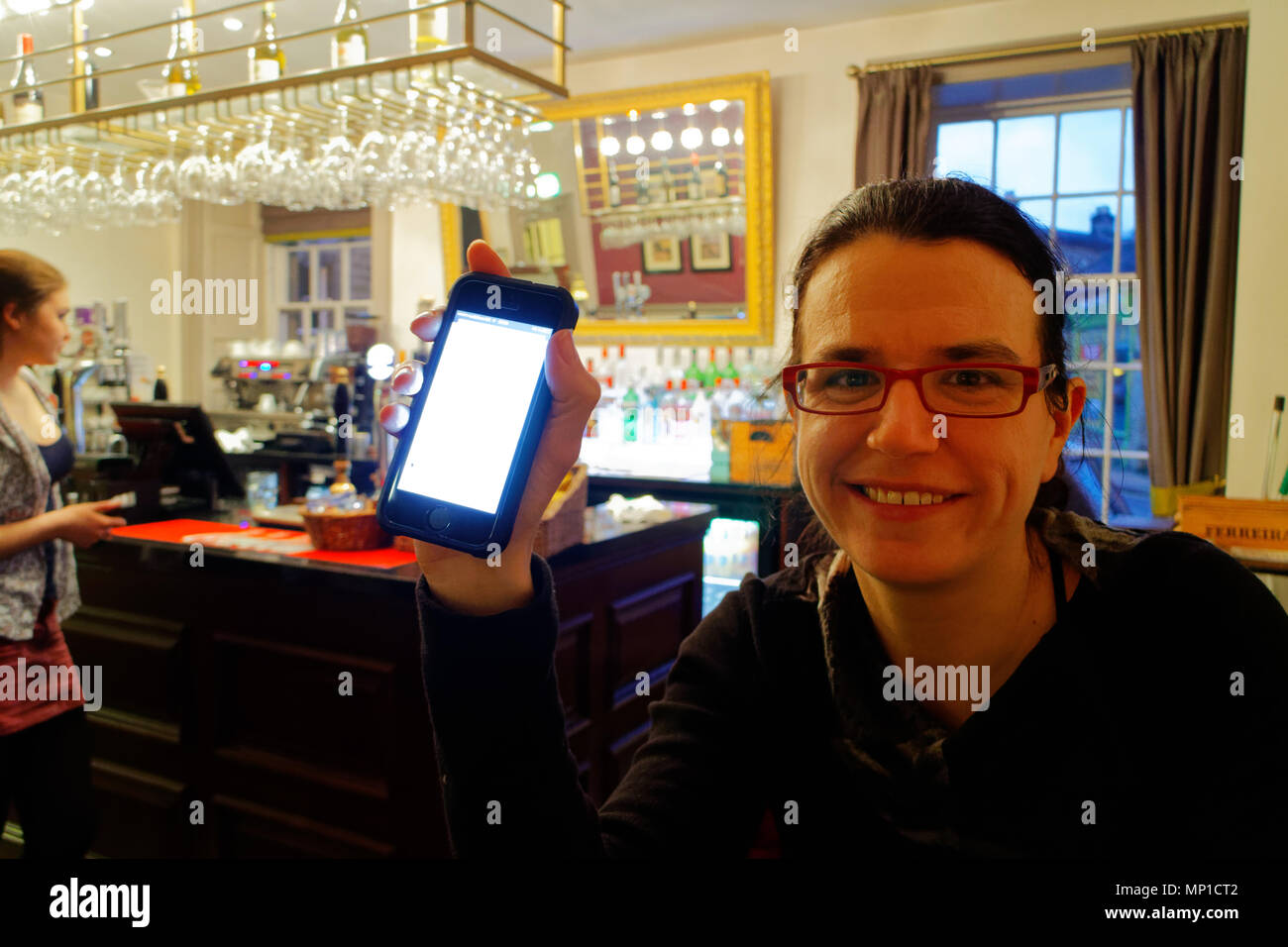 A young woman getting good news on her iphone in the bar of the Rutland Arms in Bakewell, England - Stock Image