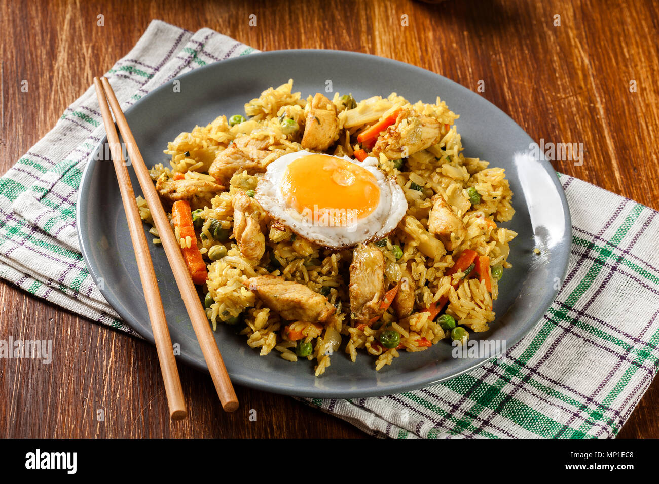 Fried rice nasi goreng with chicken egg and vegetables on a plate. Indonesian cuisine. - Stock Image