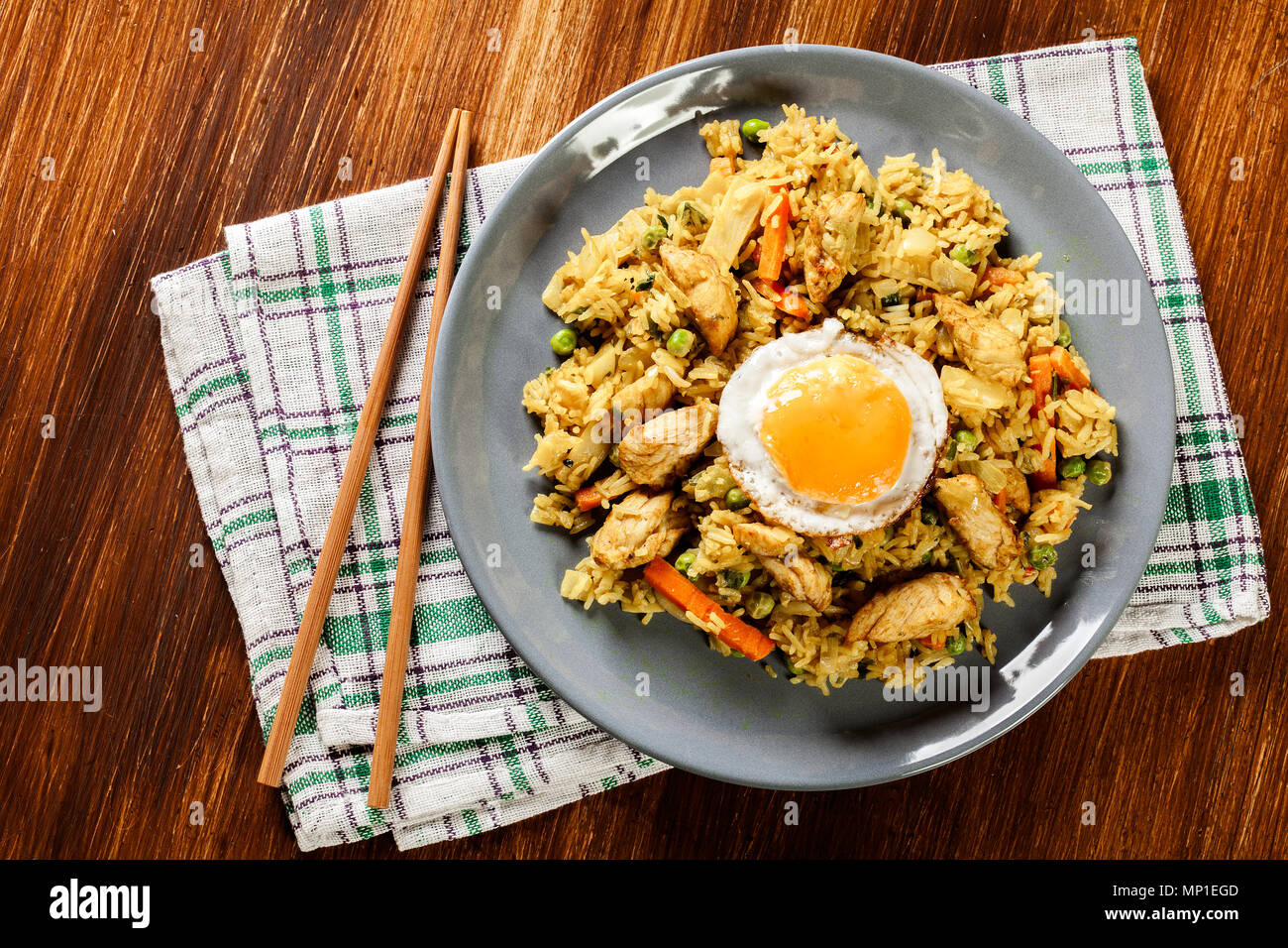 Fried rice nasi goreng with chicken egg and vegetables on a plate. Indonesian cuisine. Top view - Stock Image