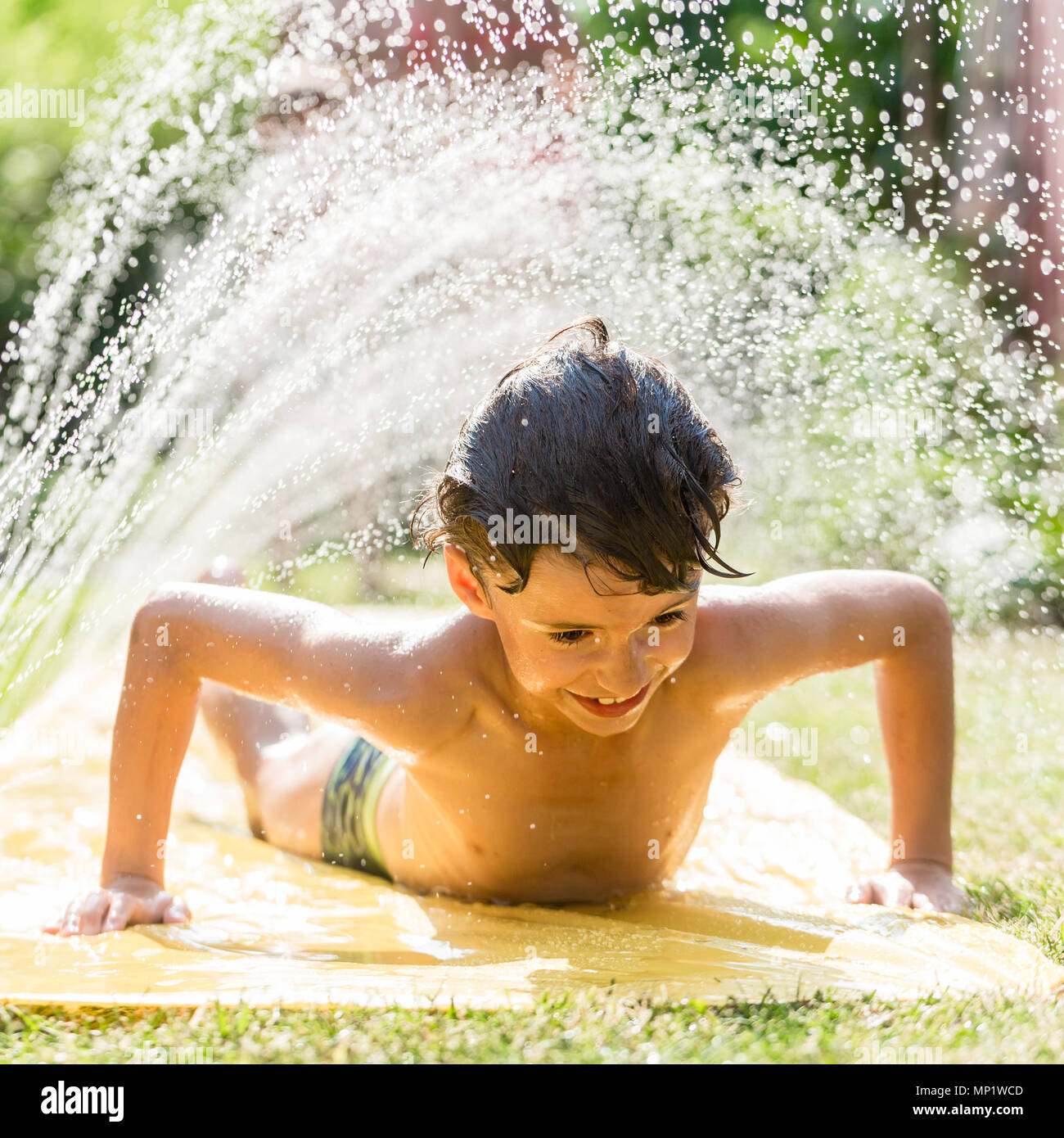 Boy cooling down with garden hose, family in the background - Stock Image