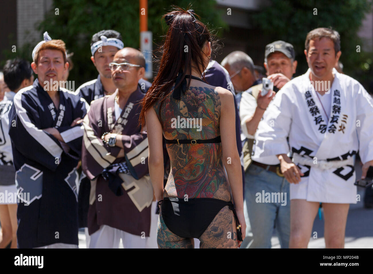 Tokyo, Japan. 20th May 2018. A woman showing her full body tattooed, possibly members of the Japanese mafia or Yakuza, poses for the cameras during the Sanja Matsuri in Asakusa district on May 20, 2018, Tokyo, Japan. The Sanja Matsuri is one of the largest Shinto festivals in Tokyo, and it is held in Tokyo's Asakusa district for three days around the third weekend of May. Credit: Rodrigo Reyes/Alamy Live News - Stock Image