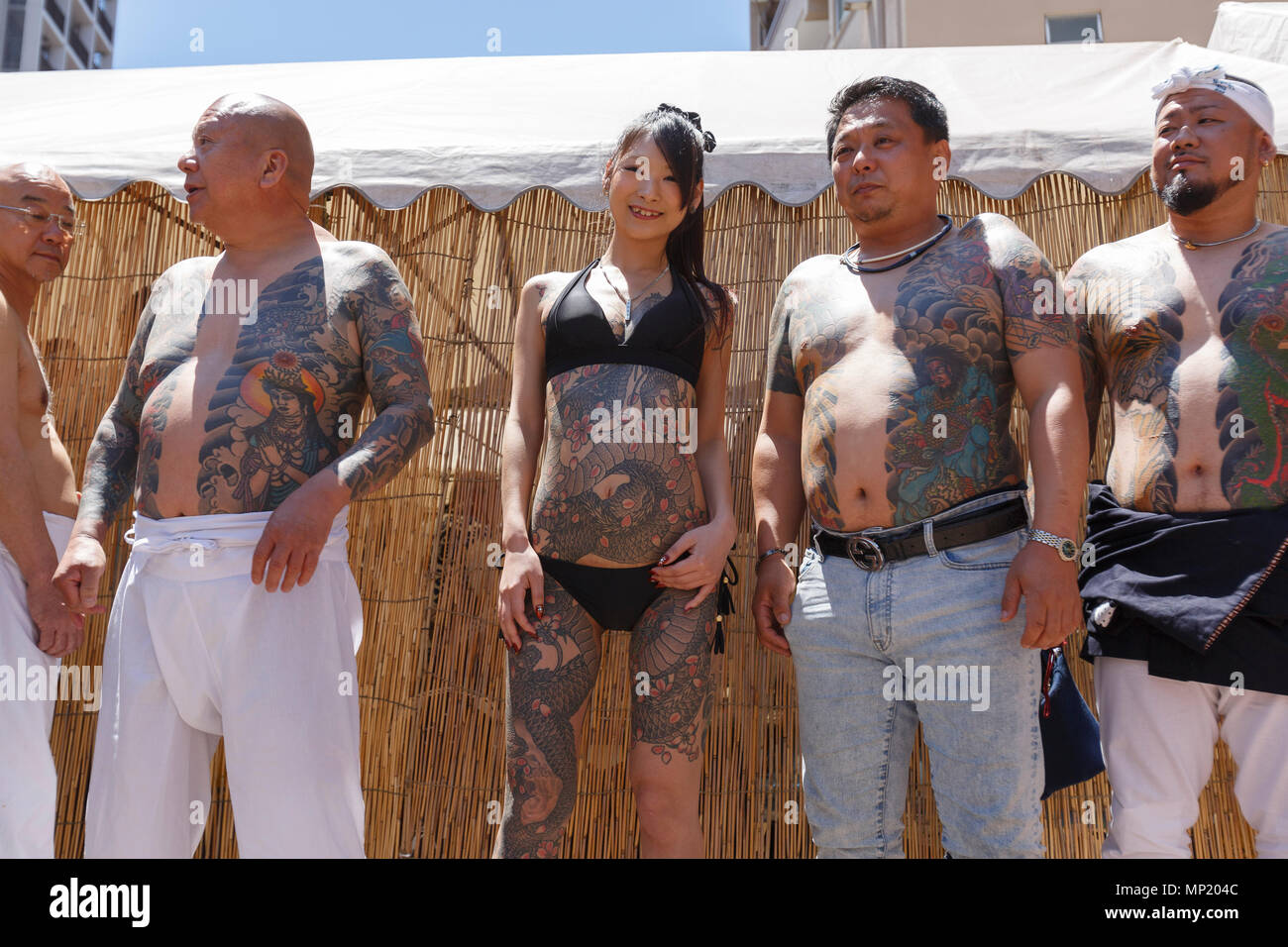 Participants showing their full body tattooed, possibly members of the Japanese mafia or Yakuza, attend the Sanja Matsuri in Asakusa district on May 20, 2018, Tokyo, Japan. The Sanja Matsuri is one of the largest Shinto festivals in Tokyo, and it is held in Tokyo's Asakusa district for three days around the third weekend of May. Large groups of people dressed up traditional clothes carry Mikoshi (sacred portable shrines) between the streets near to Sensoji Temple to bring blessing and fortune tothe inhabitants of the neighboring community at Asakusa. Stock Photo
