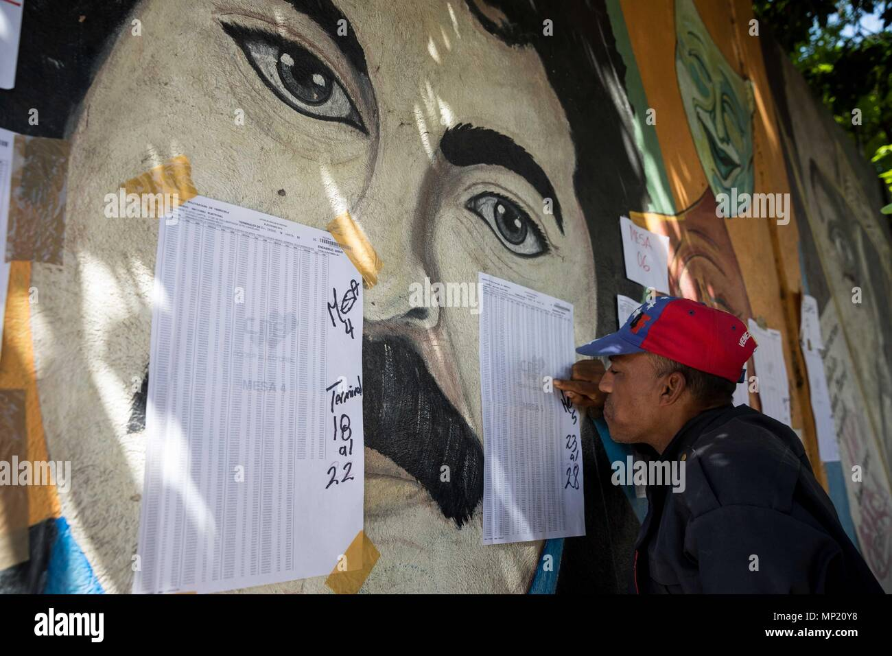Caracas, Venezuela. 20th May, 2018. Voters look for their names on a list during the Presidential election day in an electoral center in Caracas, Venezuela, on 20 May 2018. The Minister of Communication and Information of Venezuela, Jorge Rodríguez, said today that they have already voted more than two and a half million people in the presidential elections, few hours before the opening of the electoral centers. Credit: MIGUEL GUTIÉRREZ/EFE/Alamy Live News - Stock Image