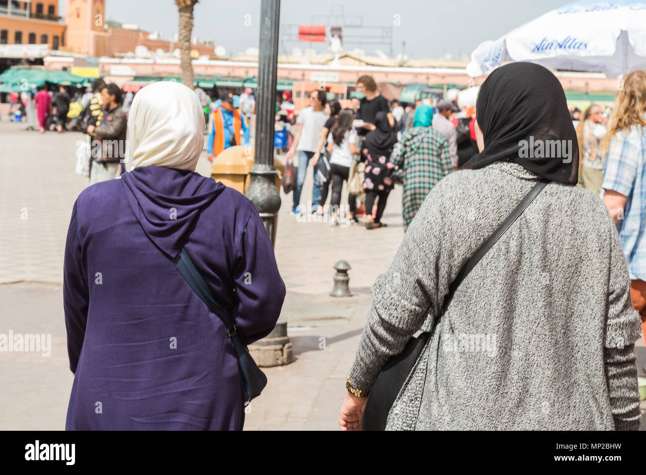 Two Islamic women walk for pizza jamaa el fna in marrakech, Morocco. - Stock Image