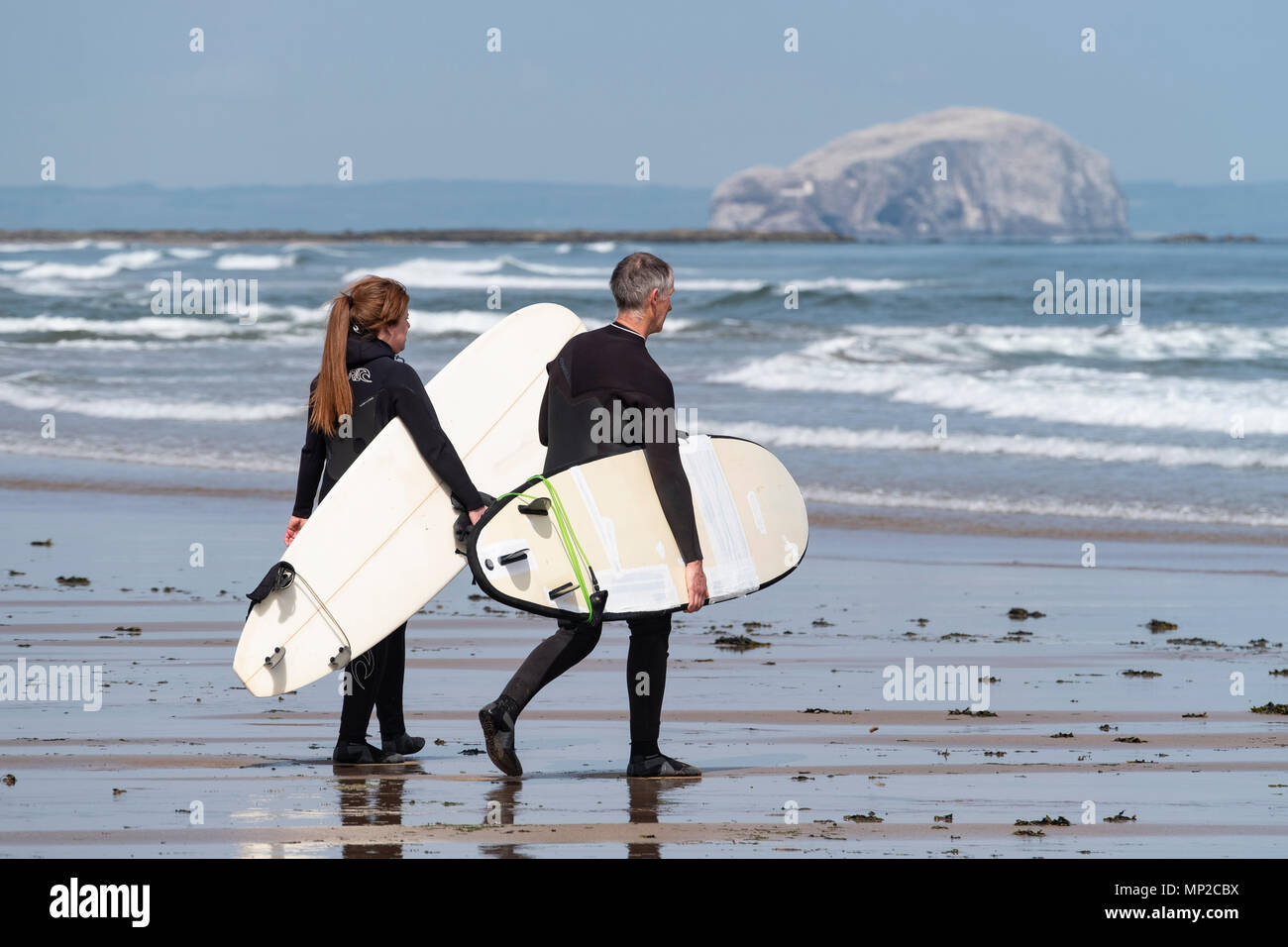Two  surfers carry surfboards to sea at Belhaven Beach, East Lothian, Scotland, United Kingdom - Stock Image