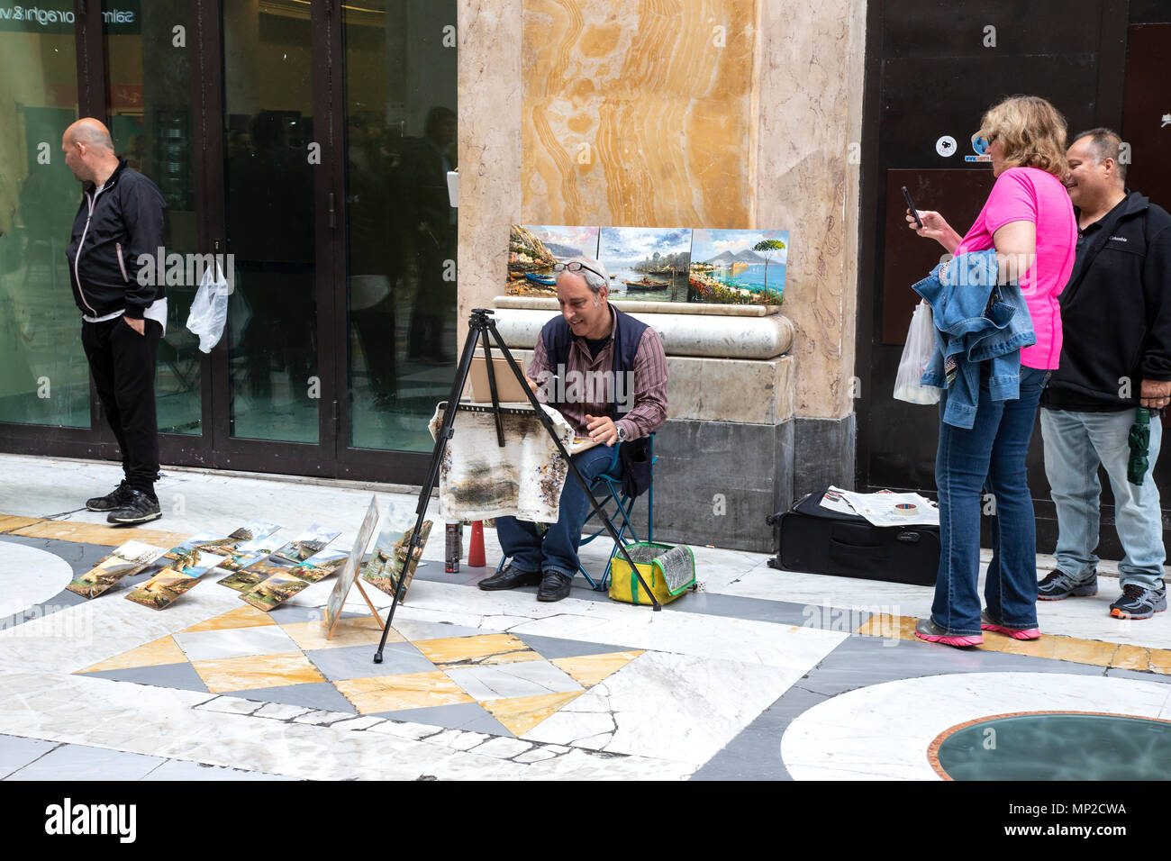 A street artist selling his work in the Galleria Umberto in Naples, Italy - Stock Image