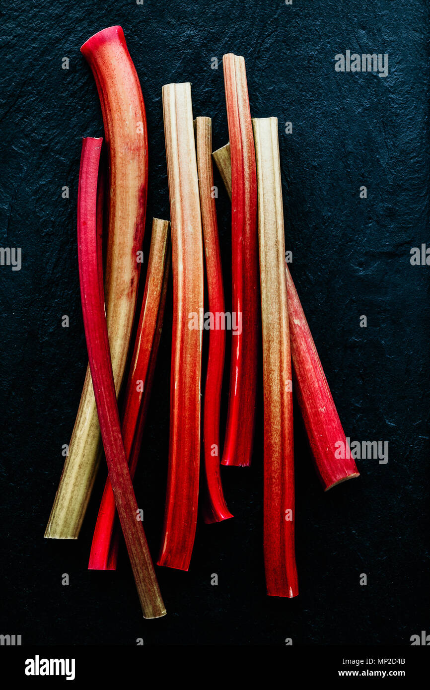 Red rhubarb stalks on black background. Minimalistic, view from above. - Stock Image
