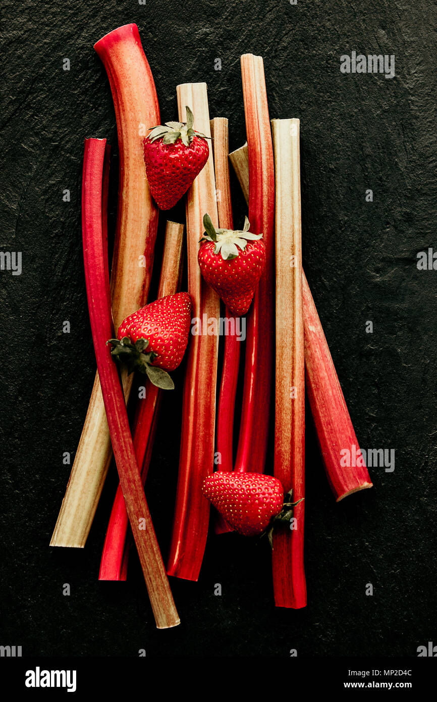 Red rhubarb stalks with red strawberries on black background. Minimalistic, view from above. - Stock Image