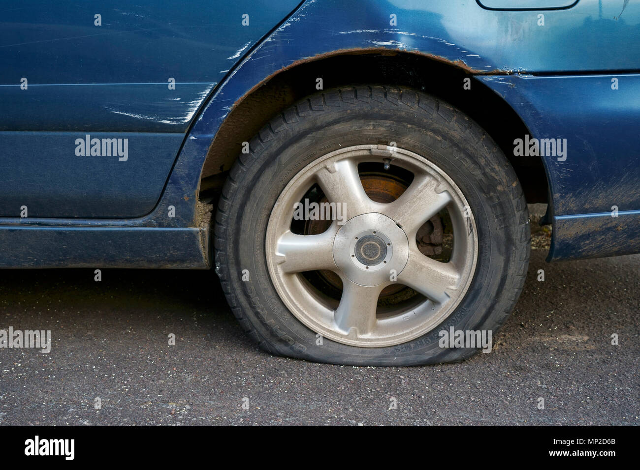 Car with a puncture and a flat tire - Stock Image