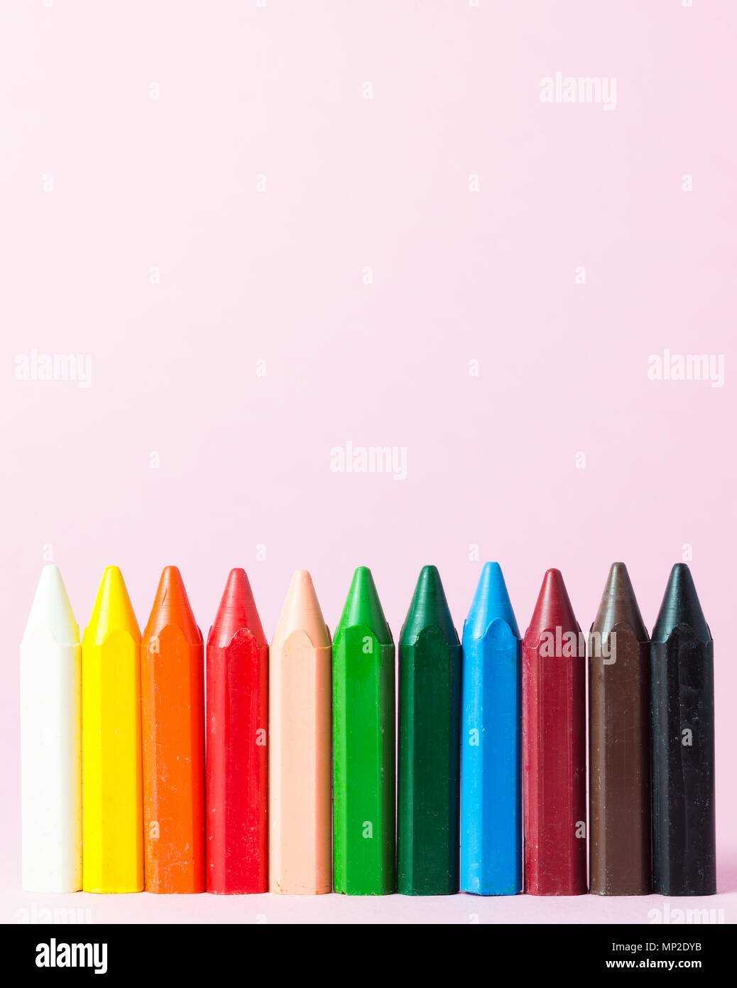New wax crayons of various colors isolated on a pink background - Stock Image
