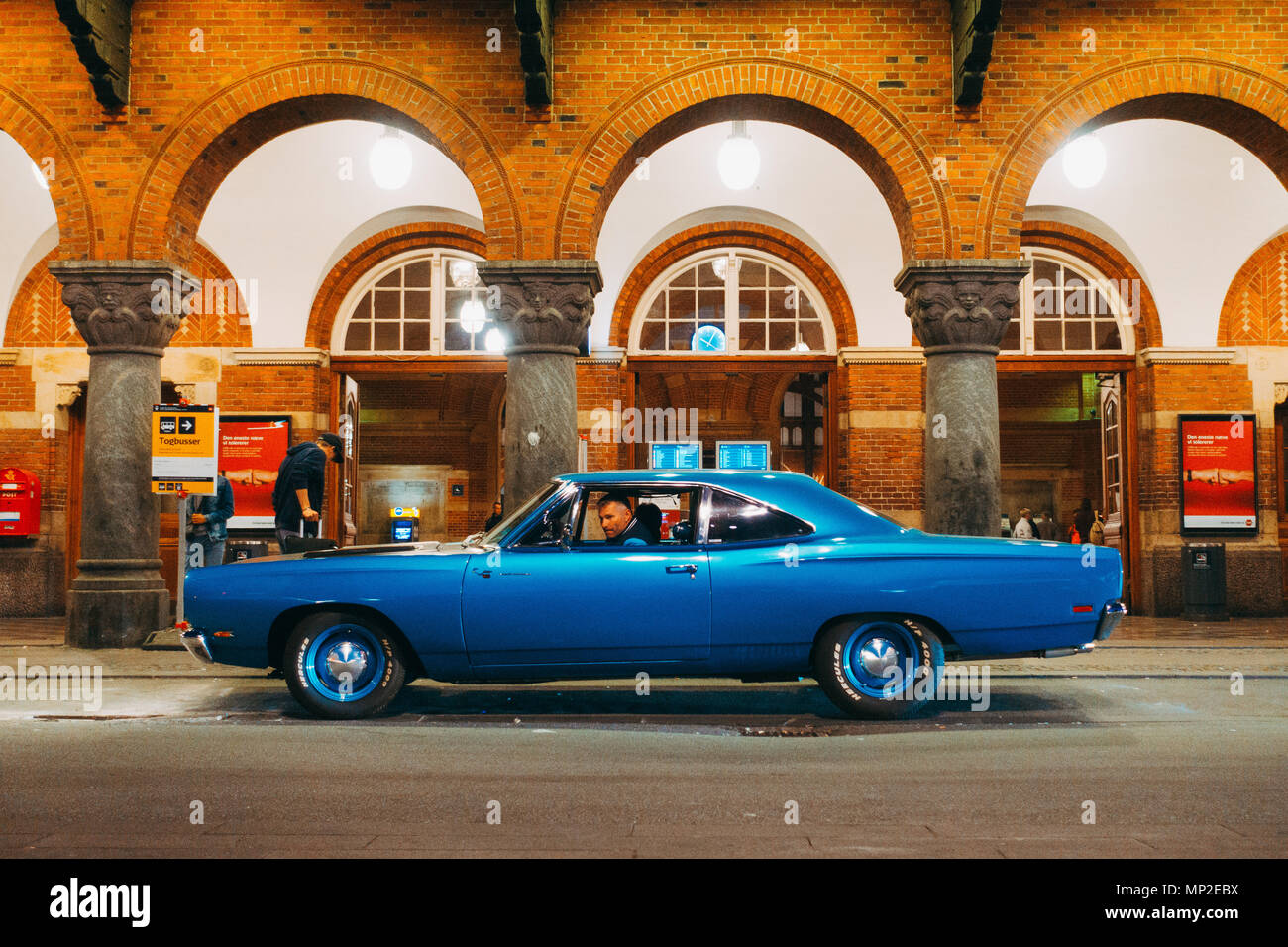 a classic 1969 Plymouth Road Runner muscle car waits outside Copenhagen Central Station, Denmark - Stock Image