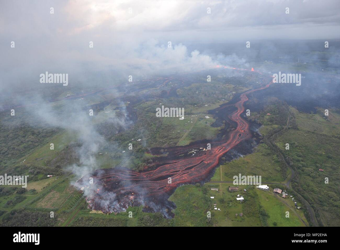 Channelized lava emerges from the elongated fissure 16-20 from the eruption of the Kilauea volcano May 19, 2018 in Pahoa, Hawaii. Stock Photo