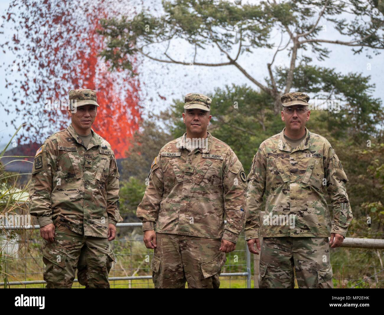 The Hawaii National Guard Joint Task Force 5-0 command team, Col. Neal Mitsuyoshi, Brig. Gen. Kenneth Hara and Col. David Williamson pose in front of a massive lava fountain spewing out from fissure 17 caused by the eruption of the Kilauea volcano May 18, 2018 in Pahoa, Hawaii. Stock Photo