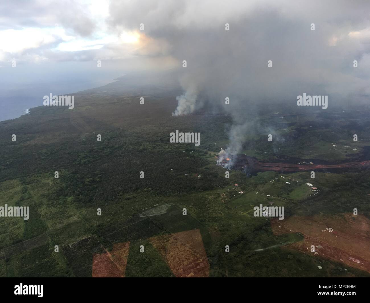 Lava and poisonous sulfur dioxide plumes rise from fissure 20 as the molten magma heads toward the ocean from the eruption of the Kilauea volcano May 19, 2018 in Pahoa, Hawaii. Hot lava entering the ocean creates a dense white plume called 'laze' (short for 'lava haze'). Laze is formed as hot lava boils seawater to dryness. The process leads to a series of chemical reactions that create a billowing white cloud composed of a condensed seawater steam, hydrochloric acid gas, and tiny shards of volcanic glass. The cloud is as corrosive as dilute battery acid, and should be avoided. - Stock Image