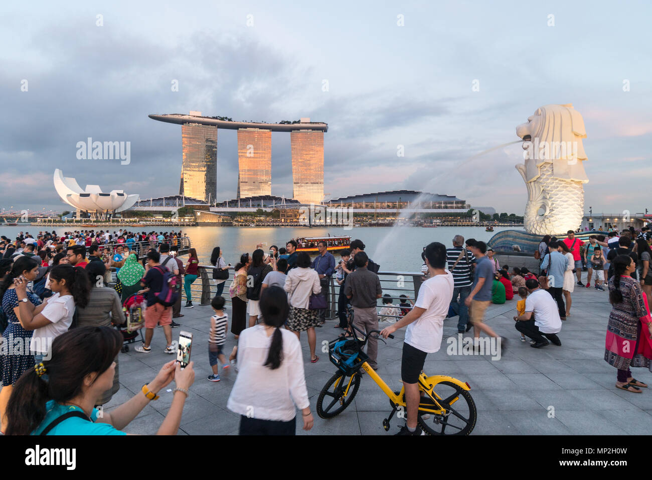 Singapore - May 13 2018: A large crowd of tourists take pictures and selfie in front of the Merlion fountain by the Marina Bay at sunset in Singapore  - Stock Image