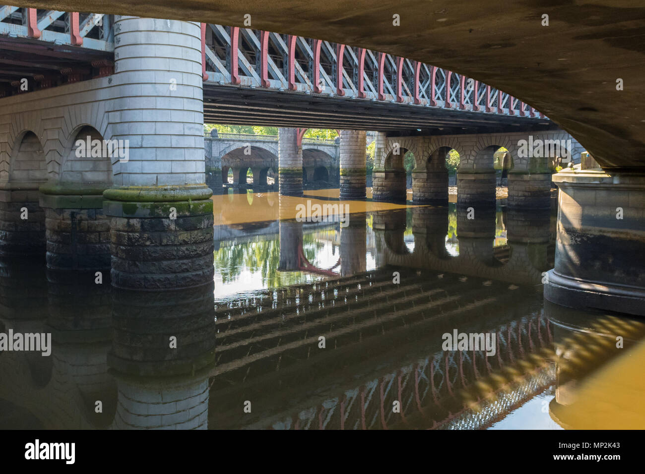 underneath Glasgow Caledonian railway bridge and King George V bridge  and the River Clyde at low tide, Broomielaw,  Glasgow, Scotland, UK - Stock Image