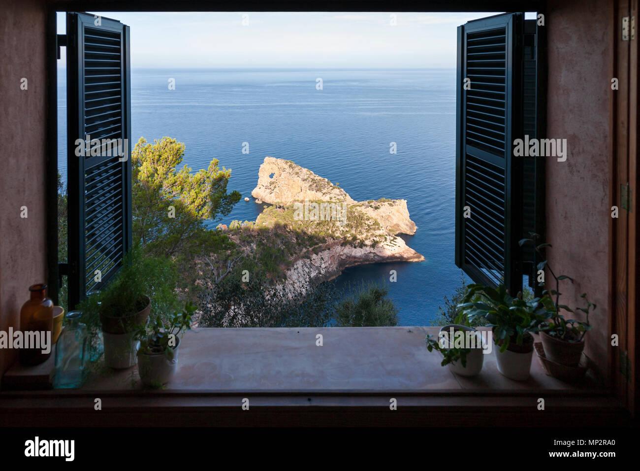 View through an open window of the Punta de  Sa Foradada Peninsula in Deia, Mallorca. - Stock Image