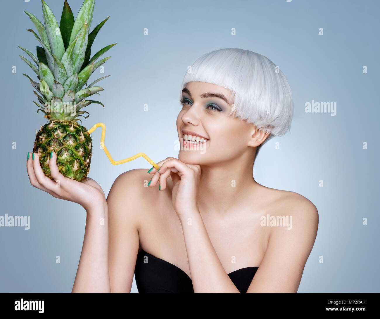 pretty young girl with pineapple cocktail photo of fashion blonde girl on blue background detox concept MP2RAH