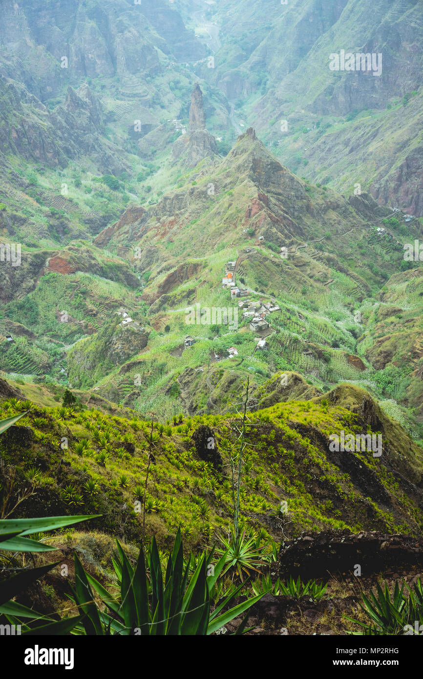 Mountain peak protrude in the middle in the green Xo Xo valley. Rugged mountain ridge overgrown with verdant grass and yucca plants spreads down the valley. Santo Antao Island, Cape Verde Cabo Verde Stock Photo