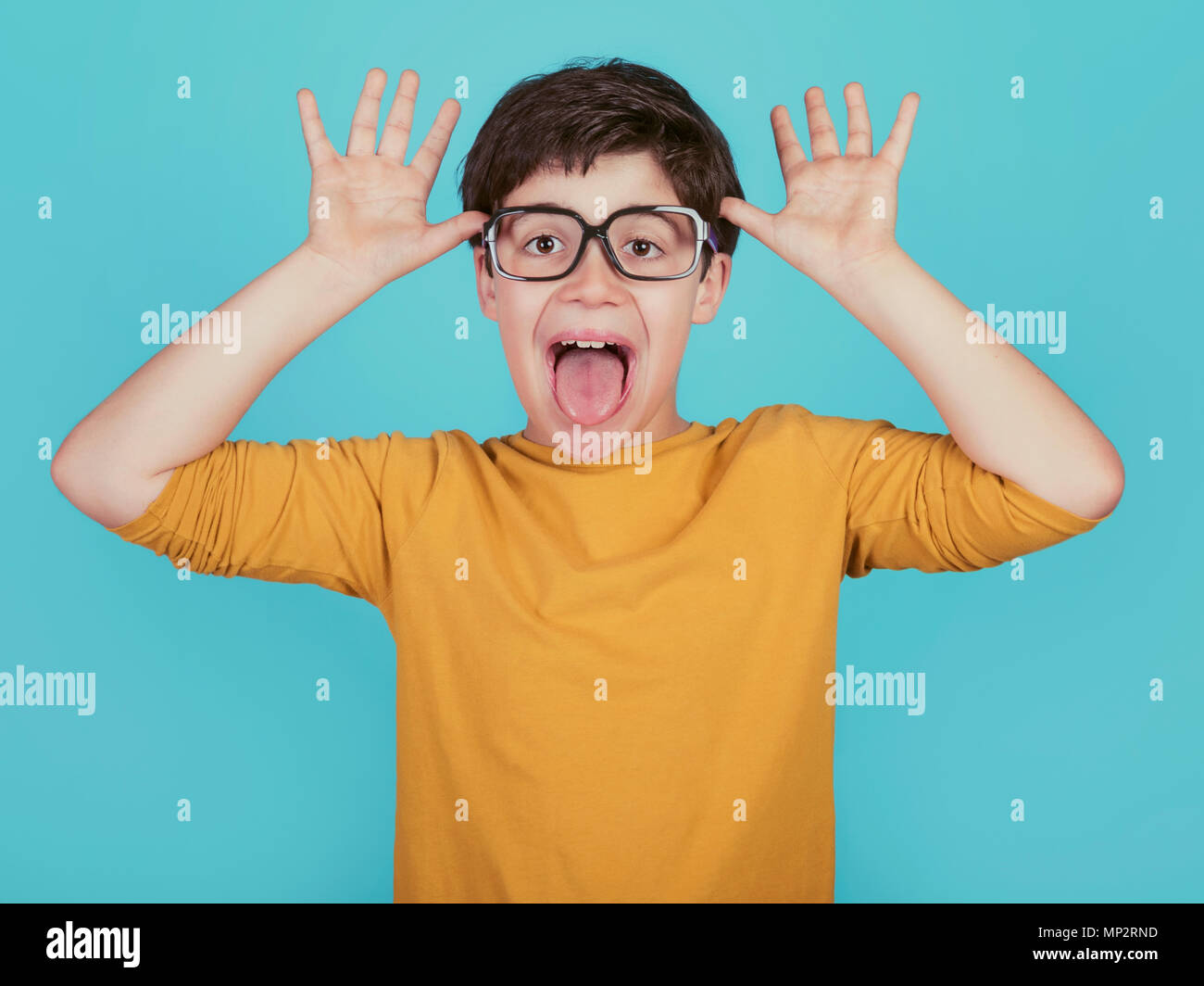 funny boy with glasses show out his tongue on blue background - Stock Image