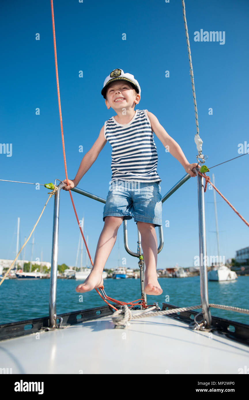 bef169e150c37 happy funny little boy in a captain s hat playing on board yacht in summer  port -