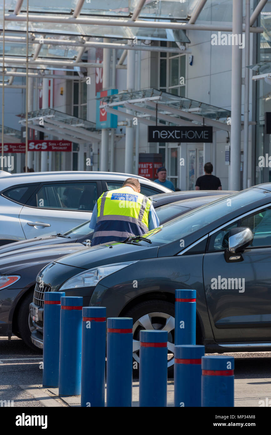 a parking attendant working in a privately controlled parking zone in a retail park at west quay shopping centre in Southampton. Private parking firms - Stock Image