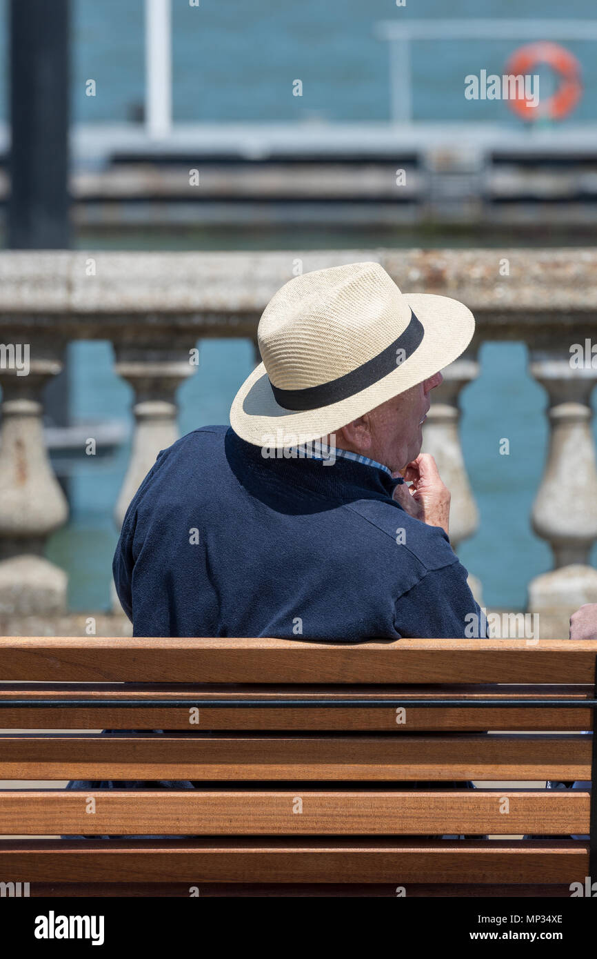 An elderly gentleman sitting on wooden bench or seat at the seaside wearing a panama or straw hat to give shade to his head from the heat. Hot weather - Stock Image