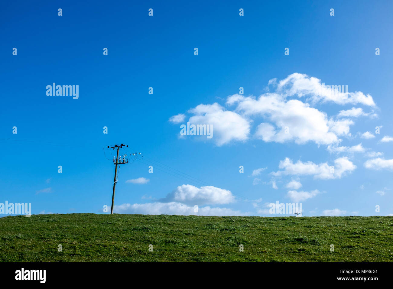 Power lines in farm land with deep blue sky and fluffy clouds in Cheshire UK Stock Photo