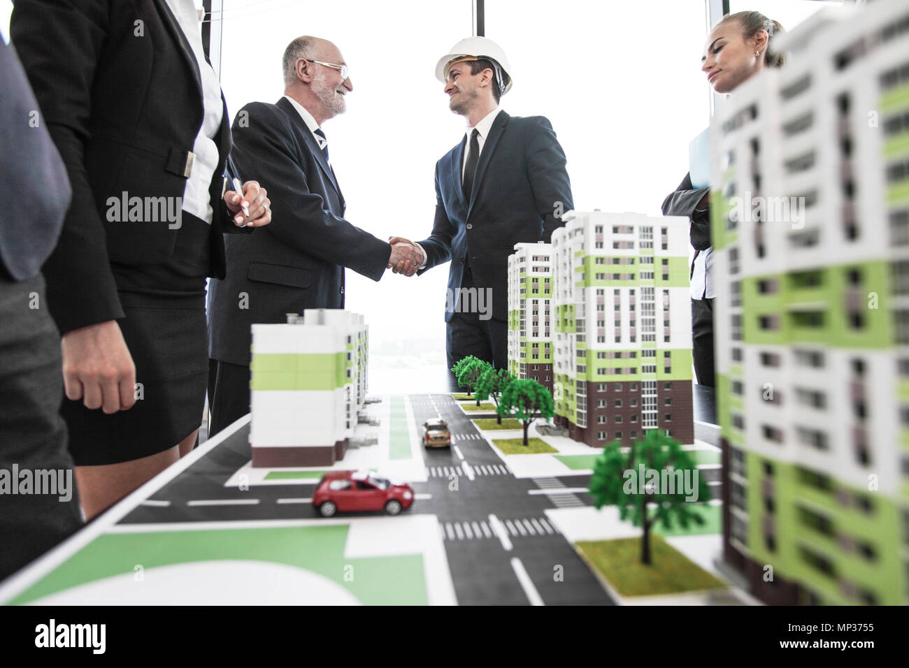 Business people standing near residential quarter houses models and shaking hands, meeting of architects and investors - Stock Image