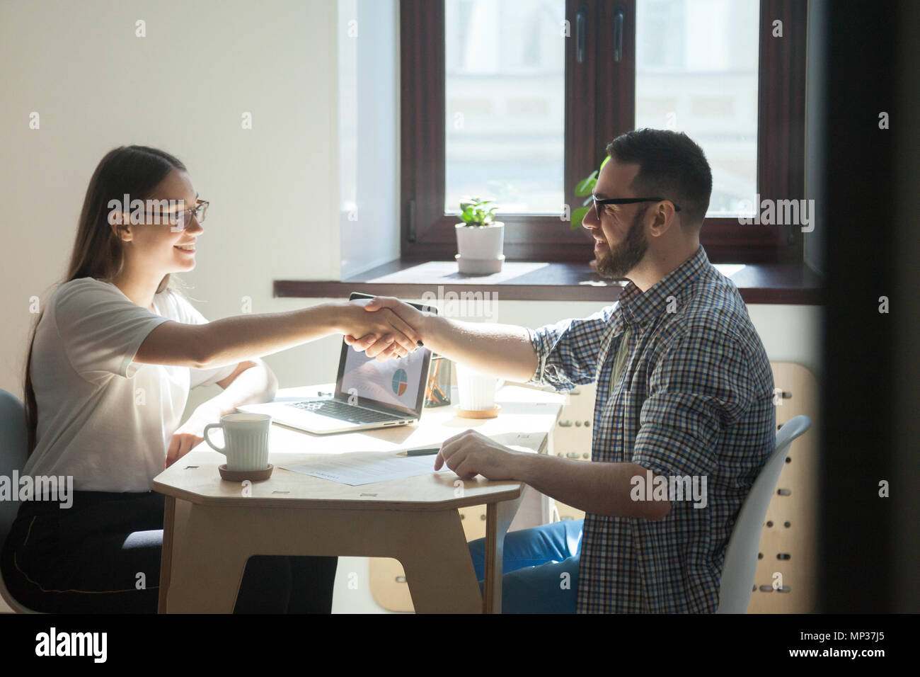 Female employer shaking hand of male job applicant - Stock Image