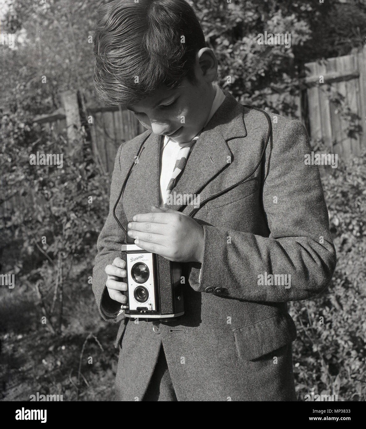1950s, historical, teenage schoolboy outside in a garden using a Kodak 'Brownie' reflex photographic film camera. This camera was made in england by Kodak Ltd from 1946 to 1960. As can be seen, to use it, one looked down at the viewfinder and held the camera at waist level. - Stock Image