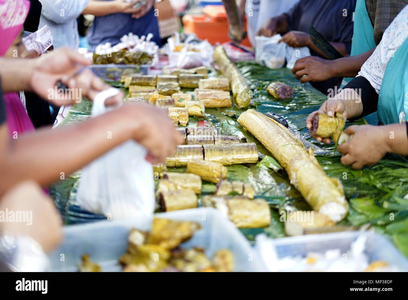 People buying Sticky Rice desserts in street food market during ramadan fasting month at Banda Aceh City, Aceh Province, Indonesia - Stock Image