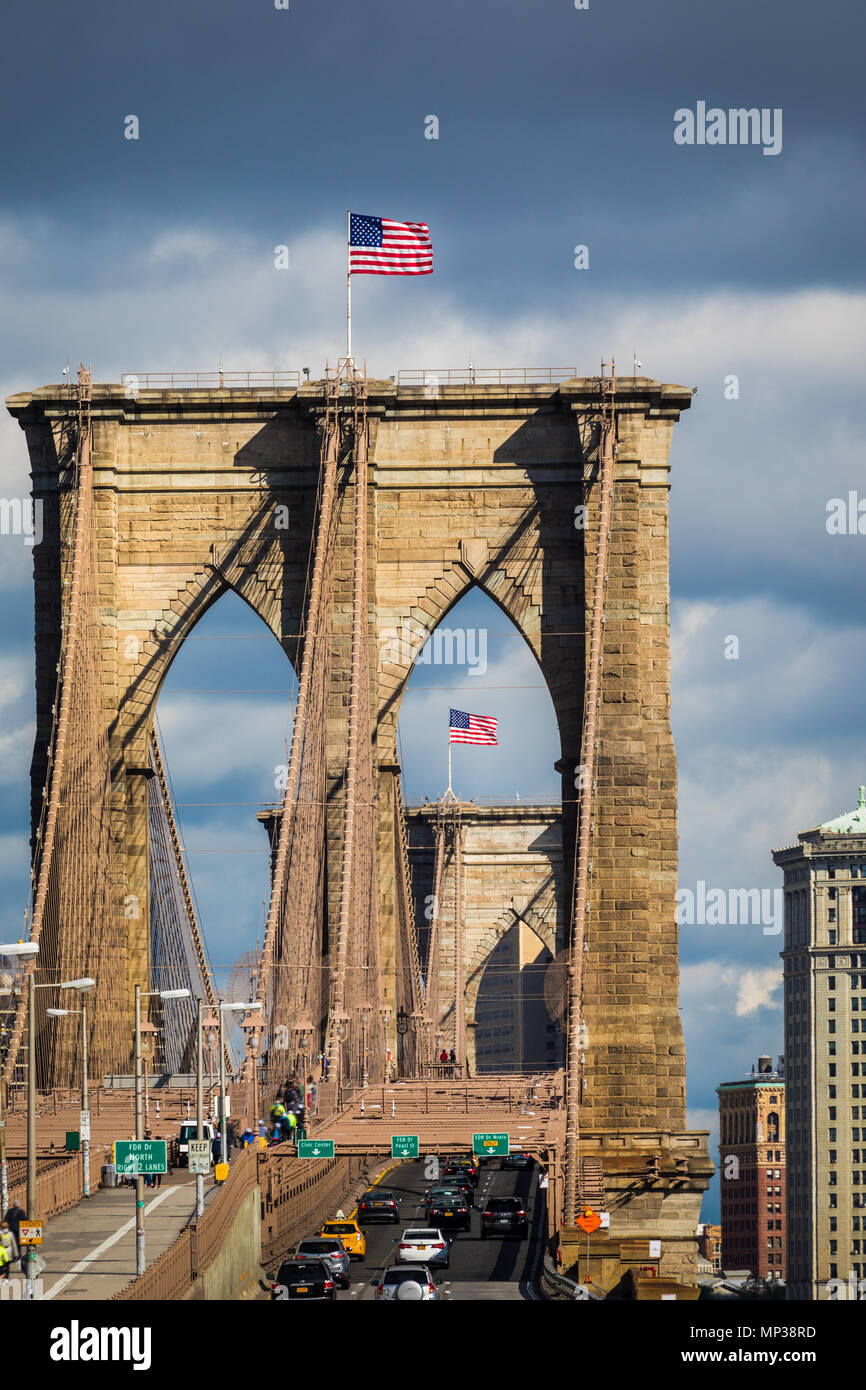 US flags fly above the Brooklyn Bridge in New York City, USA. - Stock Image