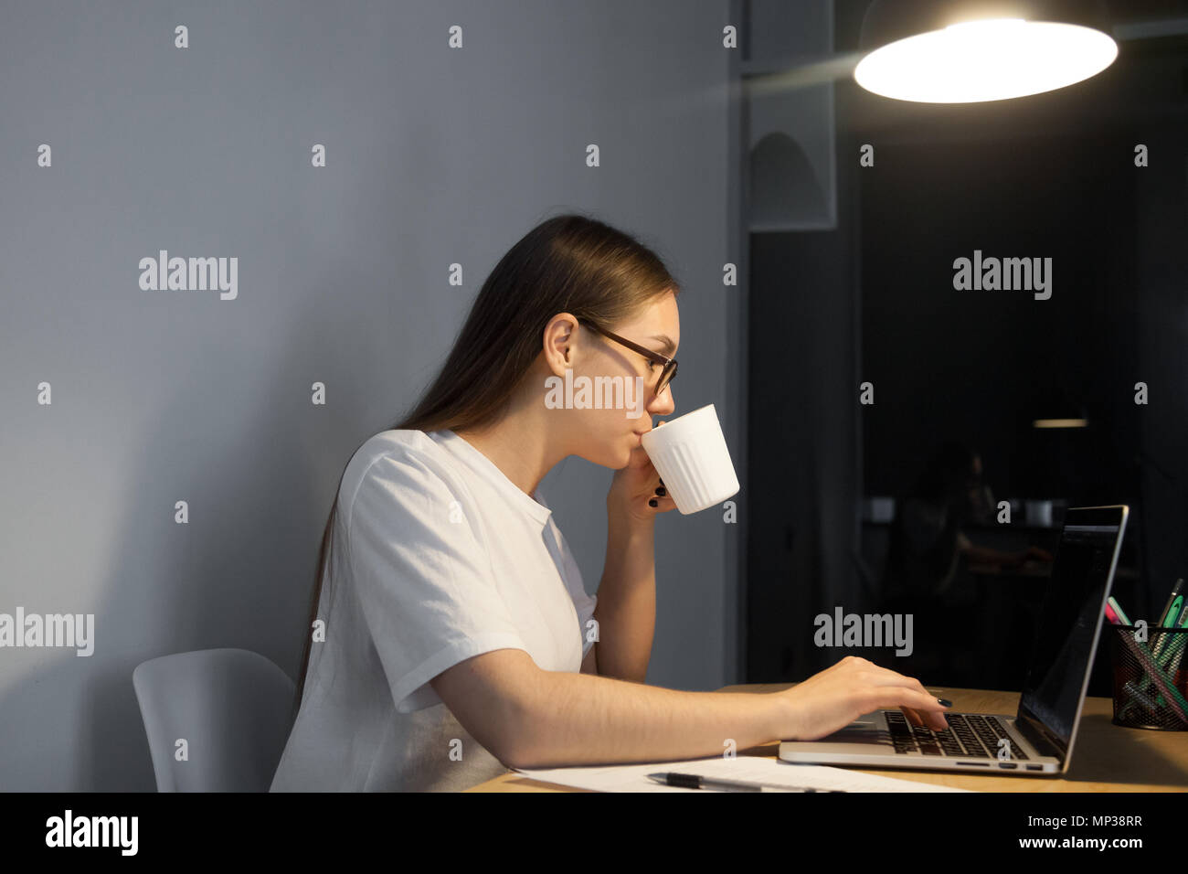 Female worker having coffee while working late - Stock Image