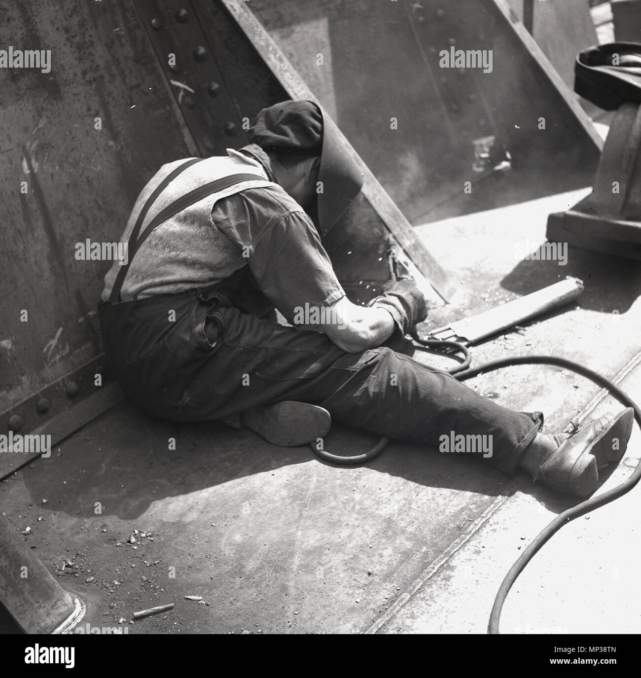 1950s, adult male worker with a face helmet or shield using a welding tool to do metalwork repairs on a ship's hull, Belfast, Northern Ireland. - Stock Image