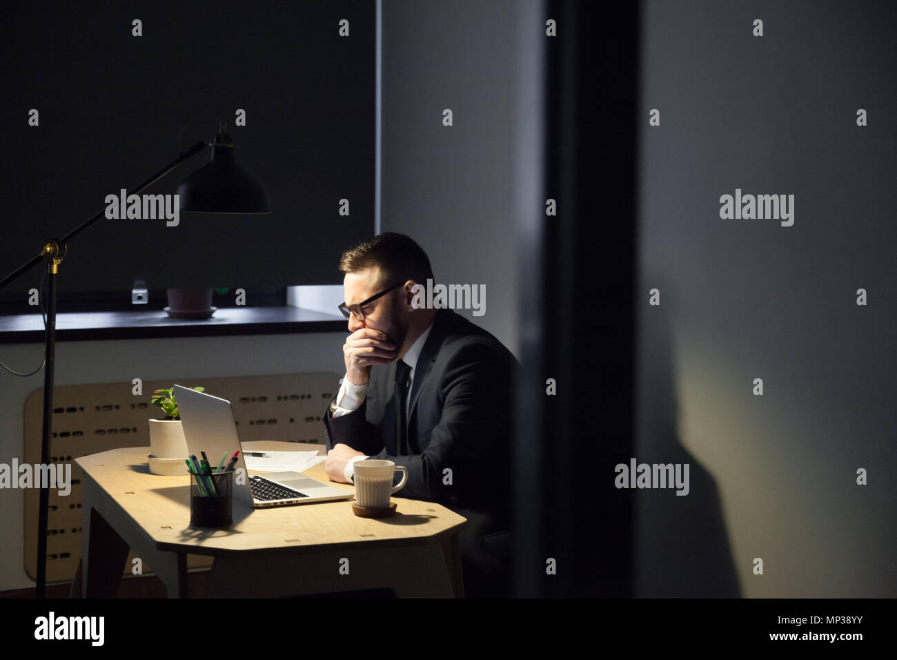 Tired male worker yawning spending late hours in office - Stock Image