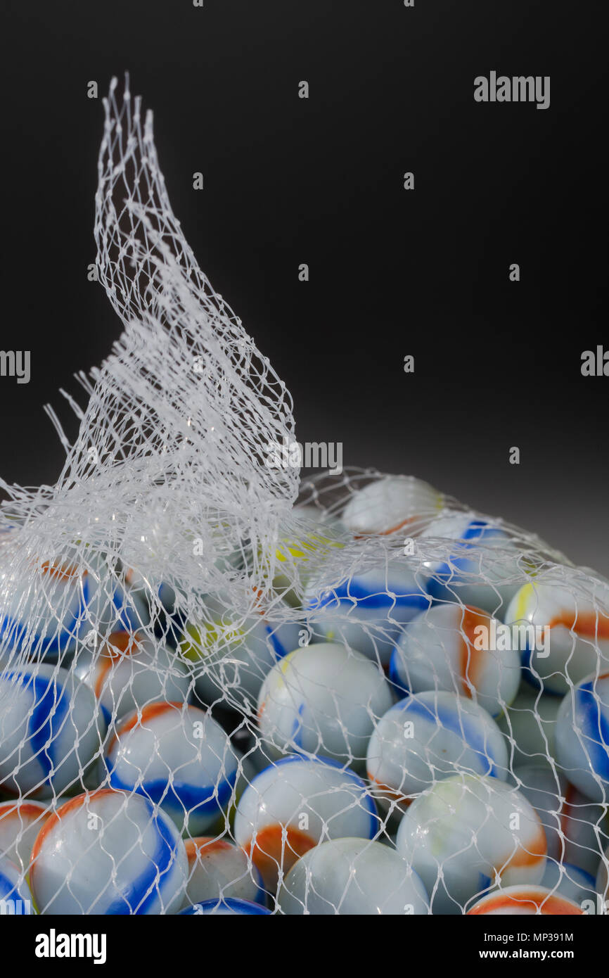 Bag of white glass marbles - metaphor Streetplay, losing your mind, something restrained /contained, bagged, in the bag idiom, marketing demographics - Stock Image