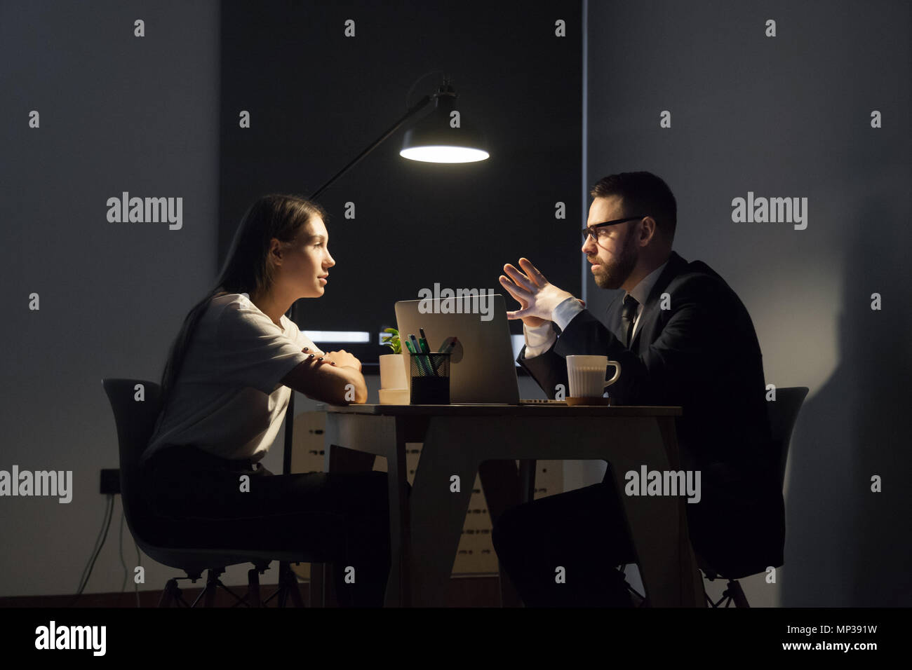 Colleagues discussing business strategies in office at night - Stock Image
