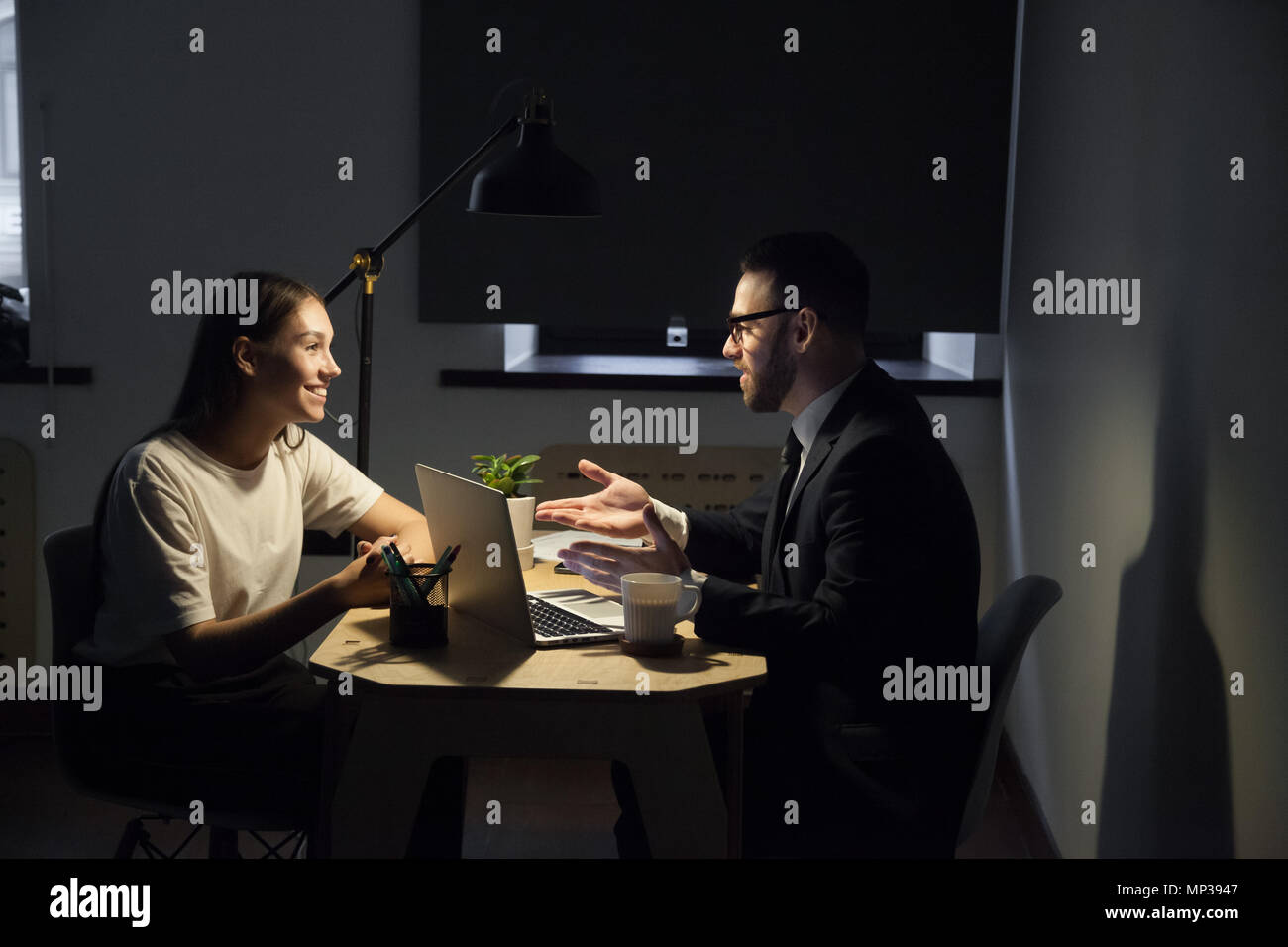 Colleagues working late hours in office discussing business plan - Stock Image