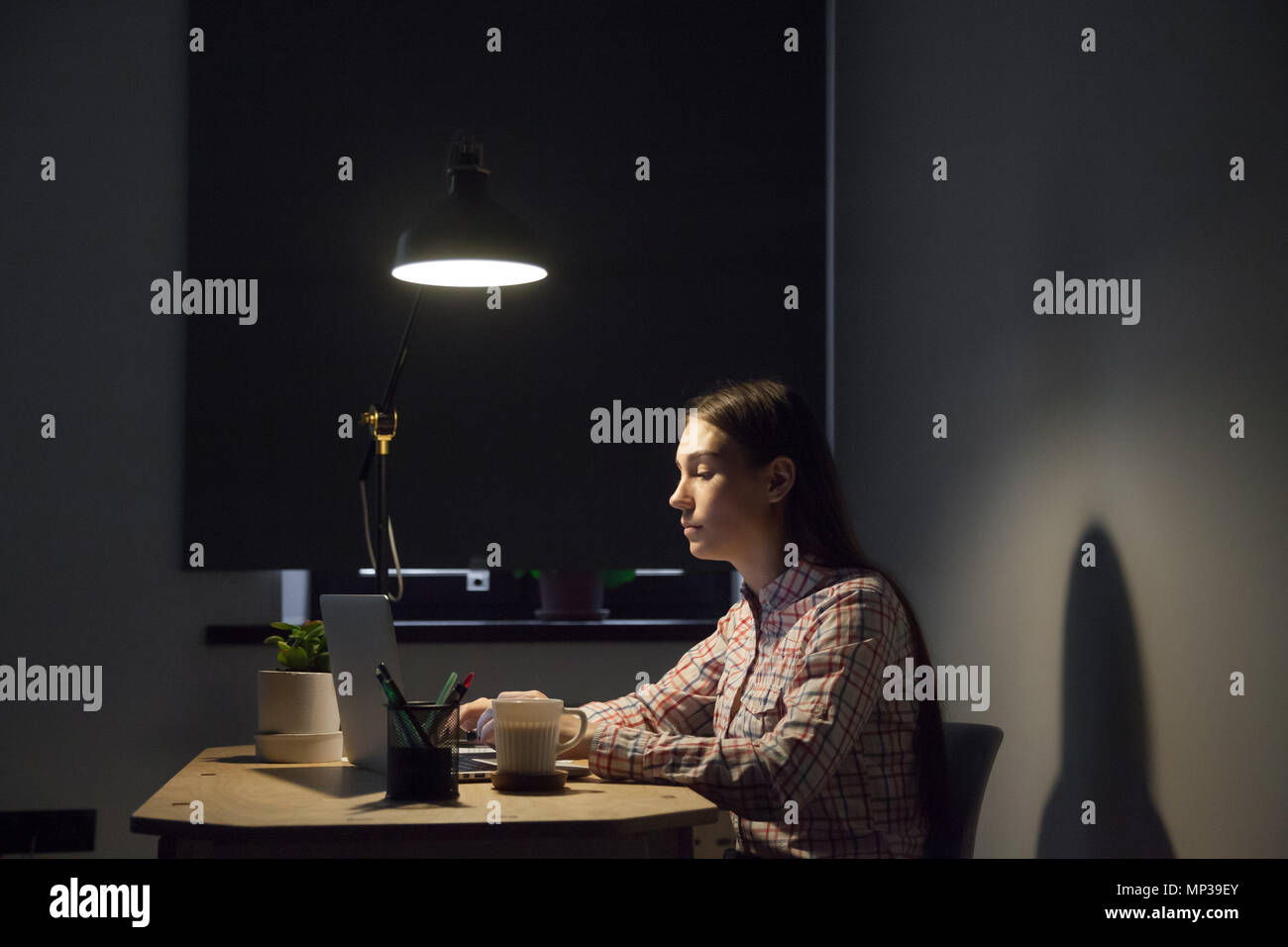 Tired female browsing information at laptop working late hours - Stock Image