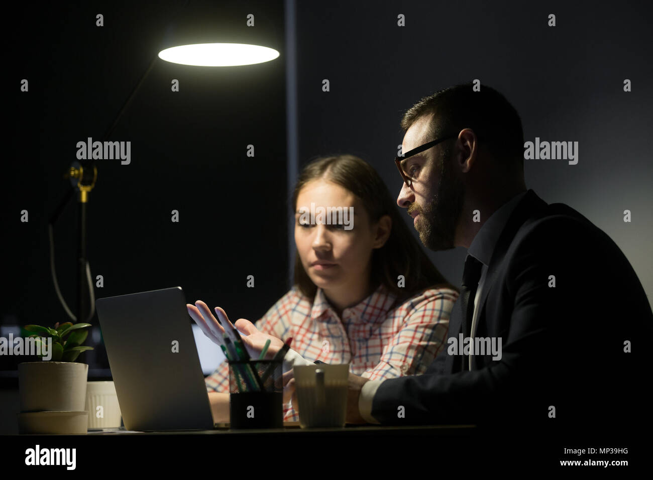 Male worker explaining marketing plans to female coworker - Stock Image