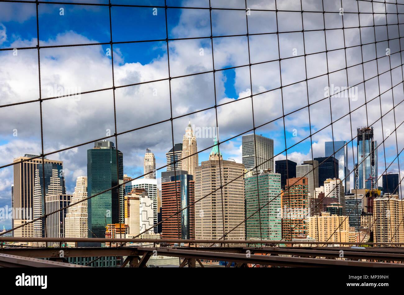 The Manhattan skyline as seen through the mesh of the Brooklyn Bridge in New York City, USA. - Stock Image