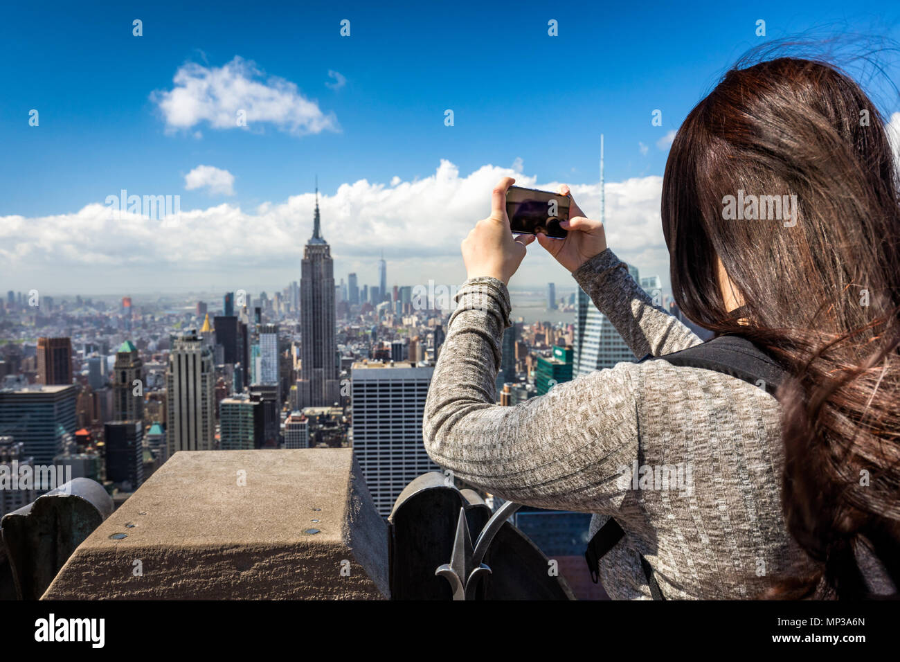 A tourist photographs the Empire State building from the Rockefeller Plaza observation deck in New York City, USA. - Stock Image
