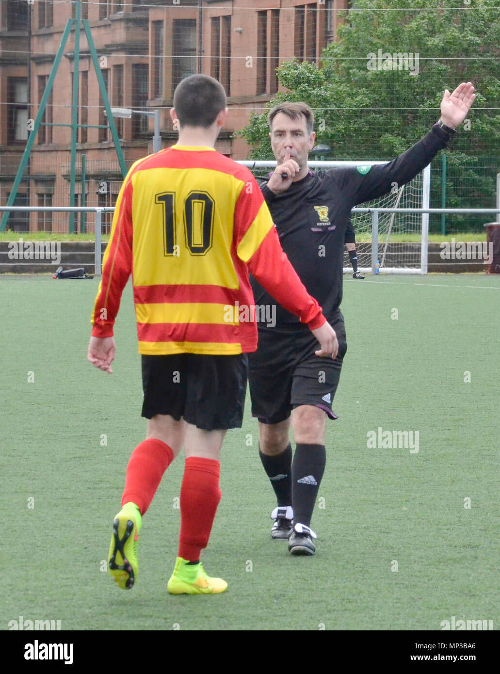 GLASGOW, SCOTLAND - JUNE 8th 2014: A referee blows his whistle while a player looks on. Stock Photo