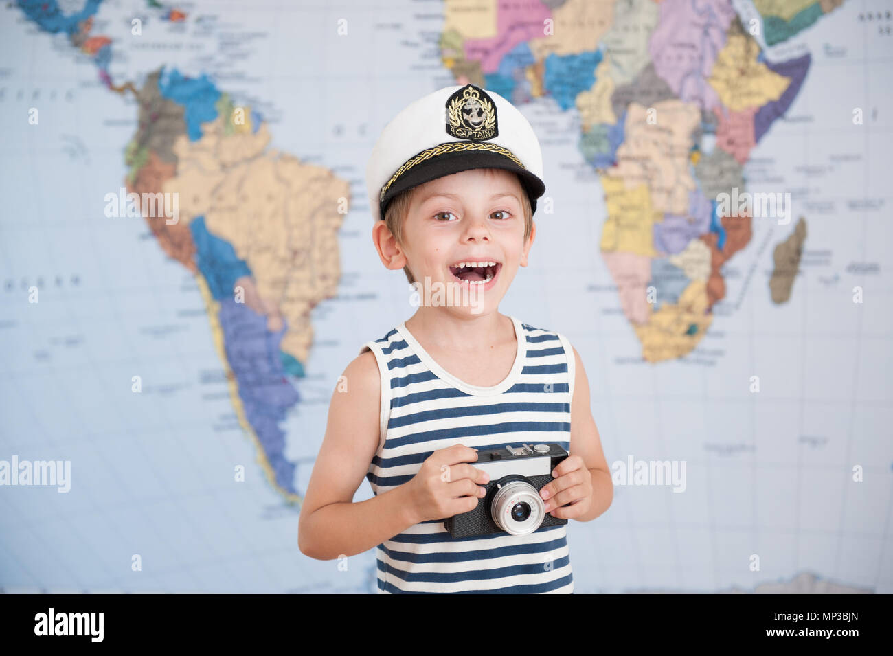 cute laughing boy in captain's hat and vintage film camera